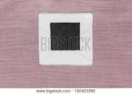 Blank clothes label on pink cloth as a background