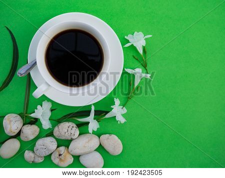 White cup of black coffee on green background
