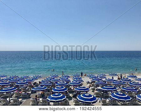 NICE - JUNE 20, 2017: Rows of Parasols create shade for deckchairs on the beach at Nice, Côte d'Azur, France.