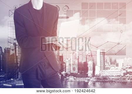 Young businessman using laptop on abstract city background with business diagrams. Toned image. Accounting concept. Double exposure
