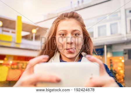 Beautiful girl taking selfie against city town shops and stores. Brunette woman holding smartphone and making self portrait with her tongue out. Hilarious picture with funny face technology concept.