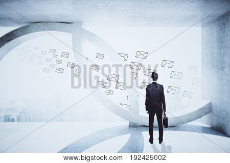 Back view of young businessman in abstract concrete interior with drawn e-mail letters and city view. Network concept. 3D Rendering