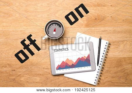 Top view of wooden office desktop with business chart on tablet screen notepad pen and coffee cup with on/off scale. Addiction concept
