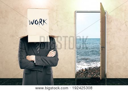 Open door with beach view and businessman with box on head in concrete interior. Work concept