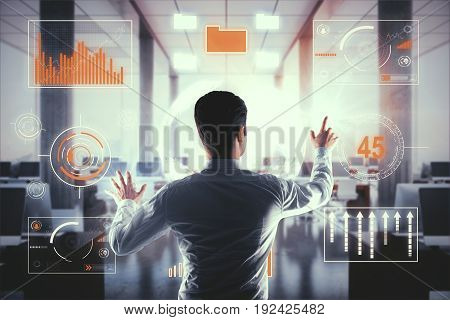 Back view of young businessman managing business charts in modern interior. Economy concept. 3D Rendering
