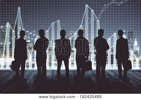 Businessmen silhouettes on city background with business charts. Finance concept. Double exposure