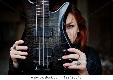 Red Haired Punk Girl Wear On Black With Bass Guitar At Abadoned Place. Portrait Of Gothic Woman Musi