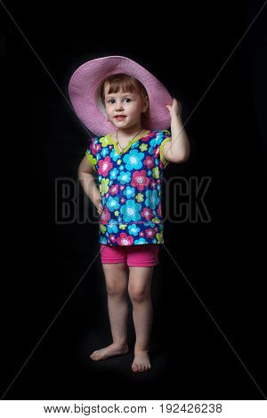 Little cheerful girl trying on a big red hat