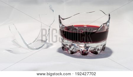 A Broken Whiskey Glass With The Remains Of Red Wine Stands On A White Background.