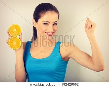 Beautiful Young Woman Showing Her Strong Bicep Muscle And Holding Slices Of Fresh Fruit Orange With