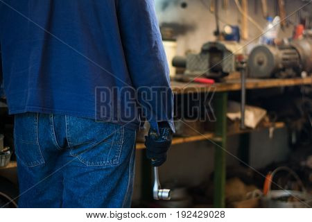 Man's hand holding a socket wrench with ratchet in the garage