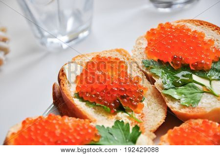 Photo of baguette with red caviar on white table.