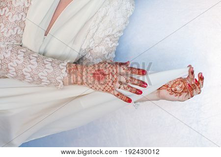 Women's hands hold a white handkerchief. Drawing of henna on hands. Body art