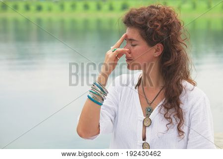 young woman practice yoga breathing techniques  outdoor by the lake healthy lifestyle concept medical alternative