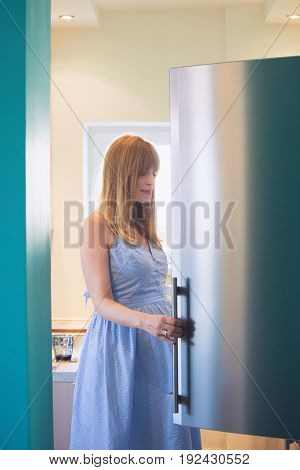 young pregnant woman in kitchen look in fridge for a snack