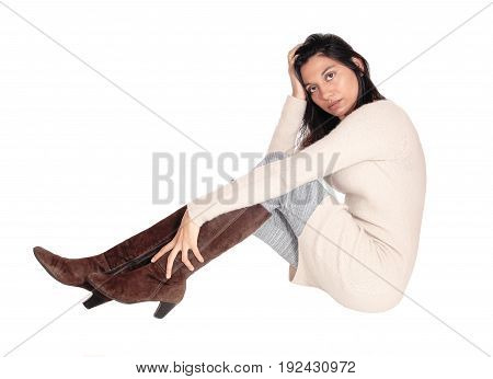 A beautiful young Hispanic woman in a knitted dress and brown boots sitting on floor the face in her hands isolated on white background.