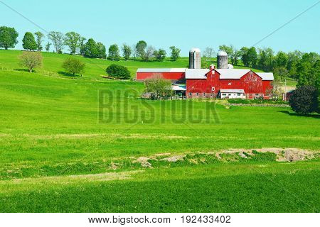 A beautiful large red farm with silos out in the country.
