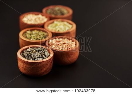 Assortment of dry tea in little bowls, on black background. Green and black tea, mint, melissa, ginger, apple, lime tree and other components for perfect beverage.