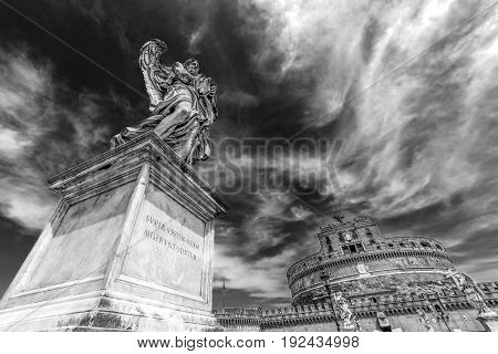 Black and white photo with statue of Angel from Angel's Bridge by sculptor Ercole Ferrata in front of castle San Angelo. Vintage processing.