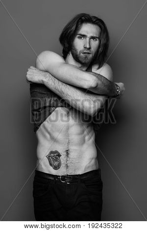 One handsome sexual strong young man with muscular body in jeans with shirt on shoulder standing posing in studio on black background