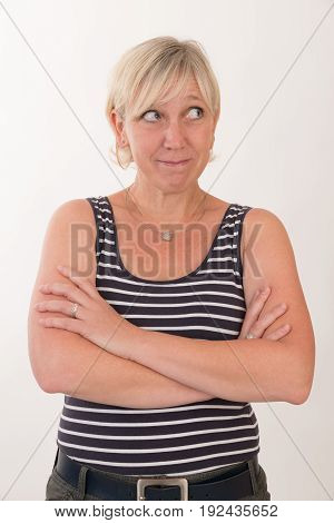portrait of a attractive blond haired mid aged european woman wearing green skirt and blue white striped top showing happy face - half body - studio shot on white background.