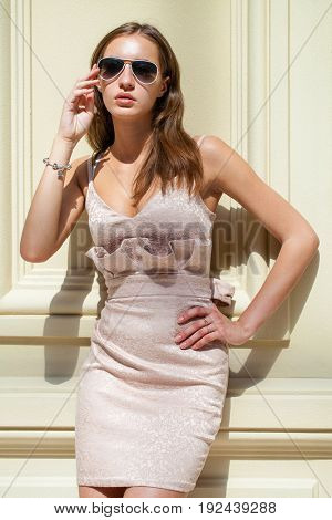 Portrait full length of young beautiful woman in beige dress, shop indoors
