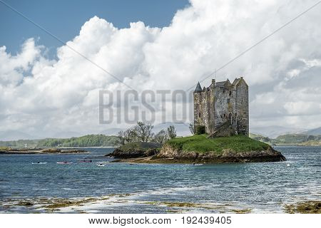 Canoes gathering at the historic castle Stalker in Argyll, Scotland
