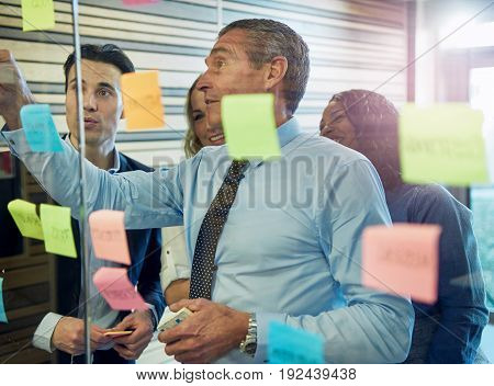 Half body portrait of businessman sticking note on glass colleagues in background