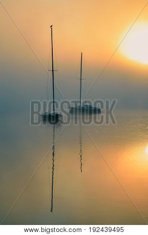 Morning foggy lake landscape. Boats on the lake with the rising sun in the background.
