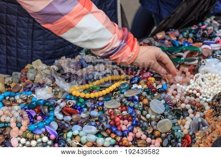 Woman chooses beads, female hand takes beads from a counter with a lot of beads