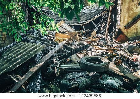Large pile of rubbish, old tires, debris of a building against the ruined house, can be used as consequences of war, earthquake, hurricane or other natural disaster