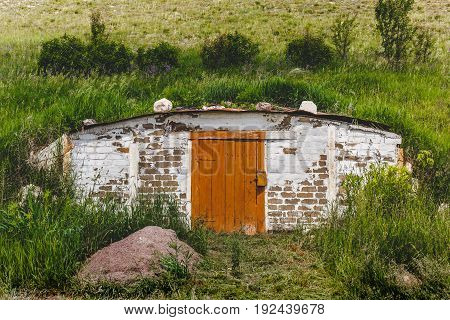 Old-fashioned rustic Dugout with a wooden door in a hill with green grass in a rural farmer's locality