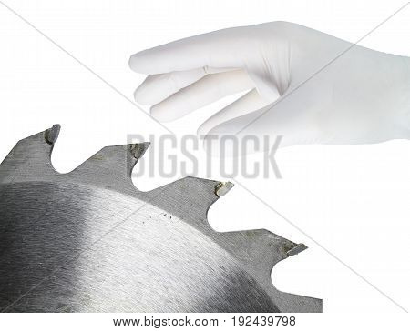 A hand in a white glove grips a dangerous saw blade.
