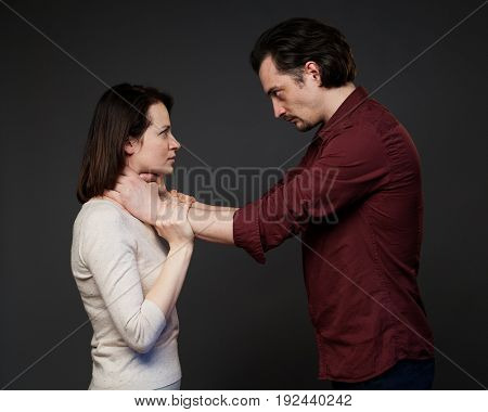 Man is choking the woman, gray background