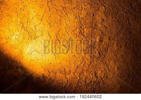 Clay wall in golden light as background .