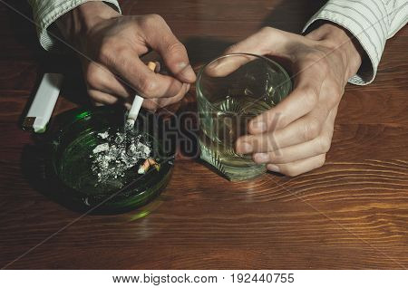 Hands with cigarette, glass with alcohol drink and ashtray on bar wooden surface. Alcohol and cigarette addiction. Depression. Sadness. Loneliness.
