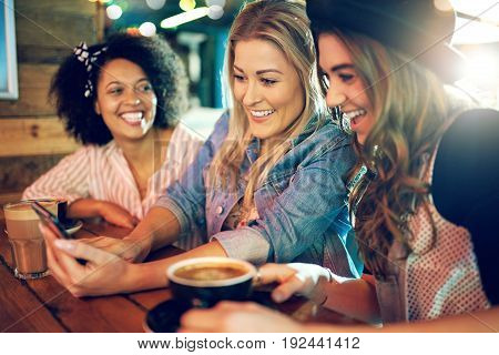 Three Young Women Laughing And Joking Together
