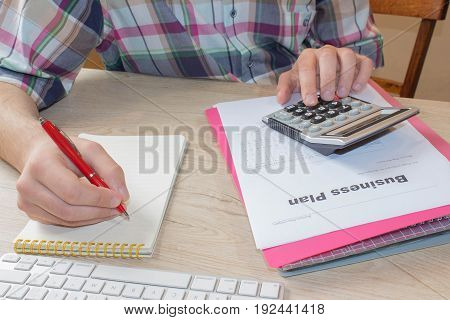 Man hand with calculator at workplace office. Business and accounting concept. A businessman doing some paperwork using his calculator