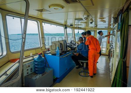 BALI, INDONESIA - APRIL 05, 2017: Ferry boat pilot command cabin with the captain operating the machines with a many assistants, in Bali Indonesia.