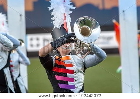 Details from a music show and marching band. Playing musicians wind instruments in uniforms.