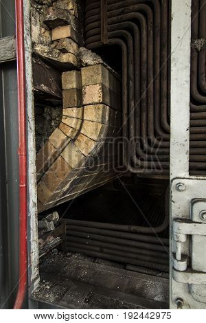 The old coal boiler grate without one wall with exposed pipes inside