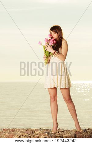 Travel romance concept. Attractive woman wearing white short dress smiling holding and smelling bouquet of tulips on beach with sea in background