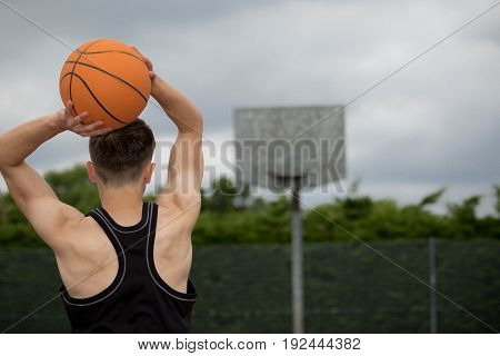 Teenage boy shooting a hoop on a basketball court
