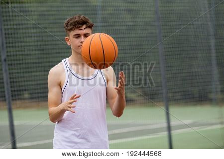 Teenage boy tossing a basketball from one hand to another on a court