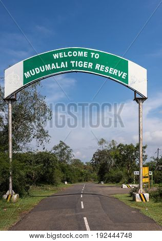 Nilgiri Hills India - October 26 2013: Mudumalai Tiger Reserve sign along road in Masamigulli Forest. Sign as gate over asphalted road. Blue sky and green vegetation.