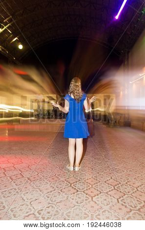 Blue dress on a girl in a disco .
