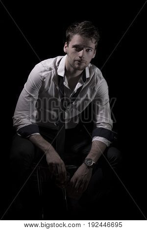 Portrait of young, attractive man in unbottoned, creased white shirt with upturned sleeves and loose tie sitting in the dark