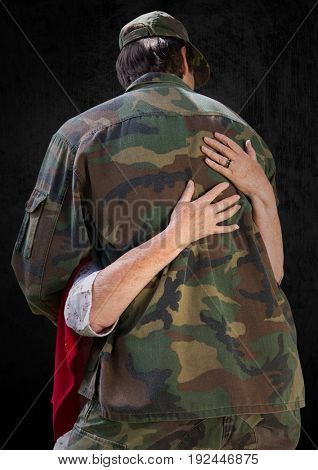 Digital composite of Back of soldier being hugged against black background