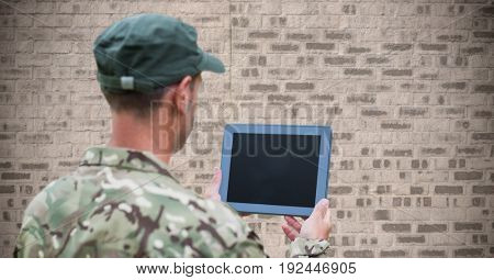Digital composite of Back of soldier with tablet against brown brick wall