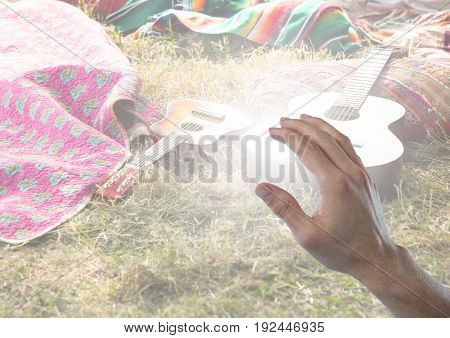 Digital composite of Hand touching festival camp site with guitars and tents